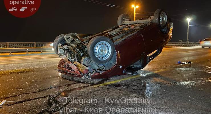 В Киеве на мосту Патона водитель Dacia совершил кульбит и приземлился на крышу: Видео